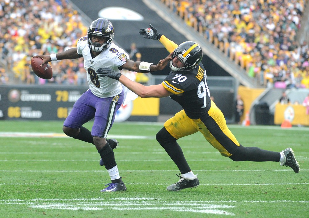 Baltimore Ravens quarterback Lamar Jackson (8) pushes away Pittsburgh Steelers linebacker T.J. Watt (90) during the first quarter at Heinz Field.