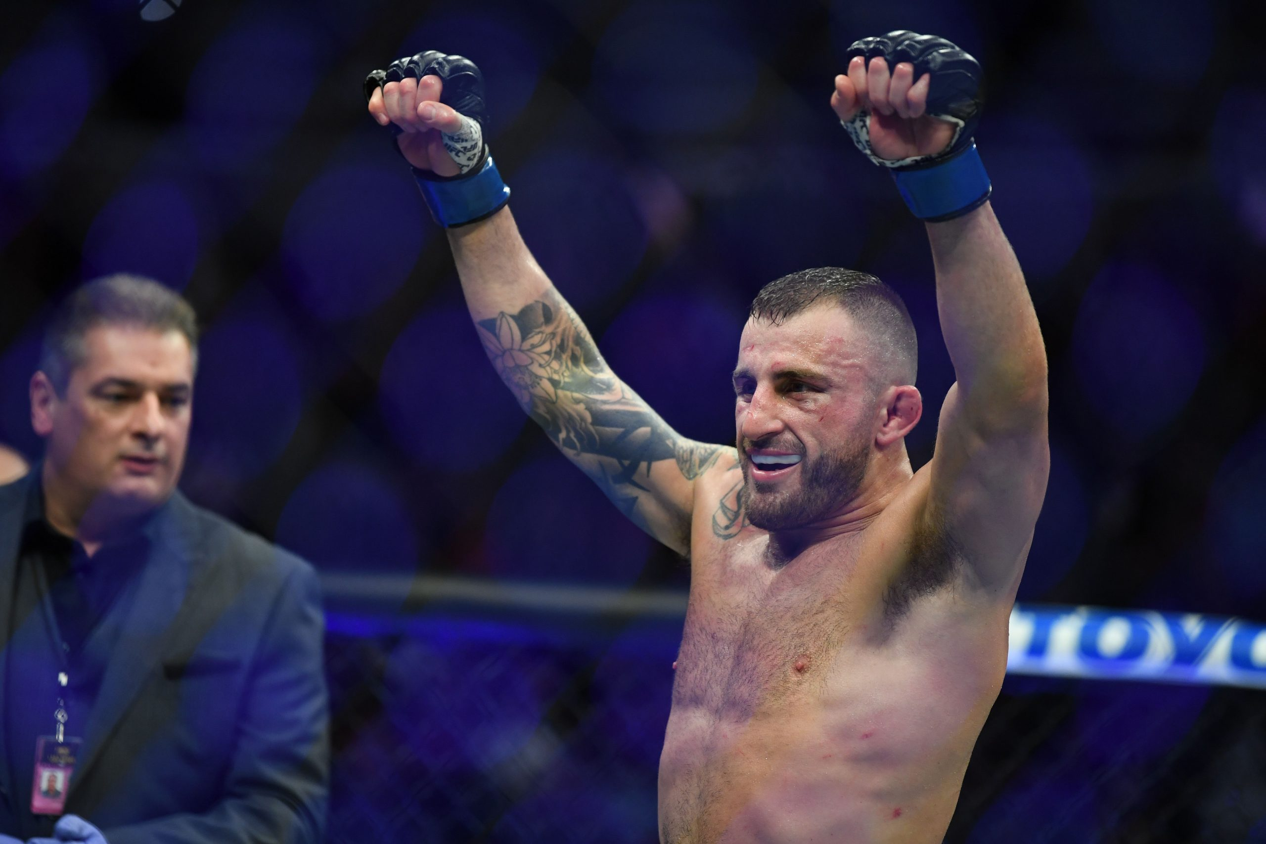 Dec 14, 2019; Las Vegas, NV, USA; Alexander Volkanovski (blue gloves) reacts after a bout against Max Holloway (not pictured) during UFC 245 at T-Mobile Arena.