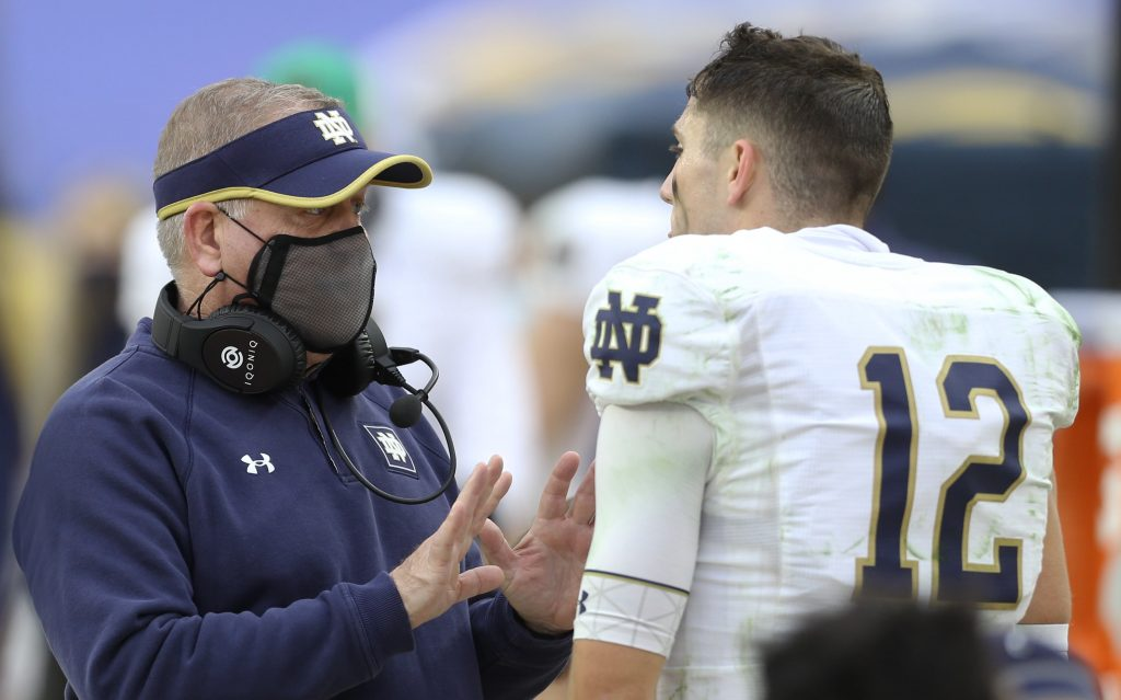 Notre Dame Fighting Irish quarterback Ian Book talks to head coach Brian Kelly during team's win over Pittsburgh