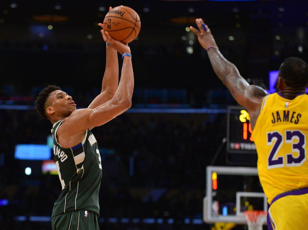 Milwaukee Bucks forward Giannis Antetokounmpo shoots over Los Angeles Lakers forward LeBron James