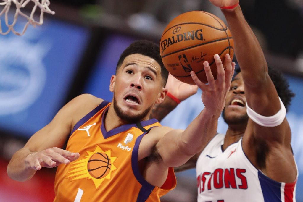 Phoenix Suns guard Devin Booker (1) goes up for a shot against Detroit Pistons guard Saddiq Bey (41) during overtime at Little Caesars Arena.