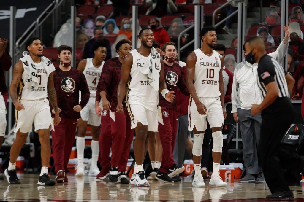 Florida State seminoles basketball players celebrate a win over the Louisville Cardinals