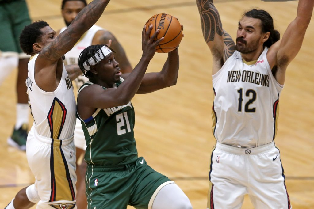 Milwaukee Bucks guard Jrue Holiday (21) drives against New Orleans Pelicans guard Eric Bledsoe (6) and center Steven Adams (12) in the second half at the Smoothie King Center.