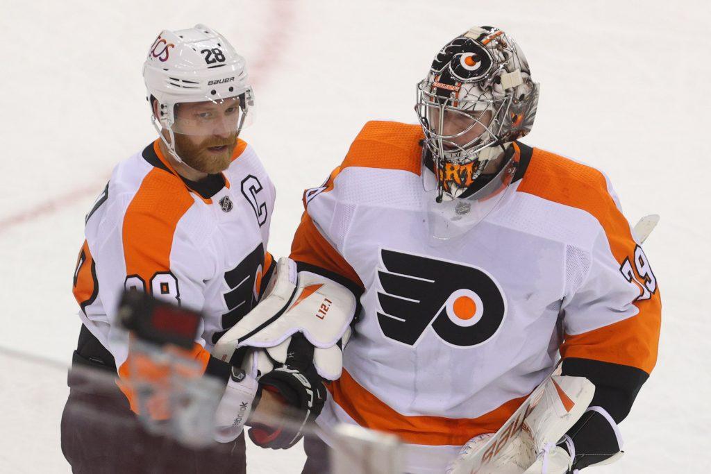 Philadelphia Flyers center Claude Giroux and goaltender Carter Hart (79) celebrate the Flyers' 3-1 win over the New Jersey Devils