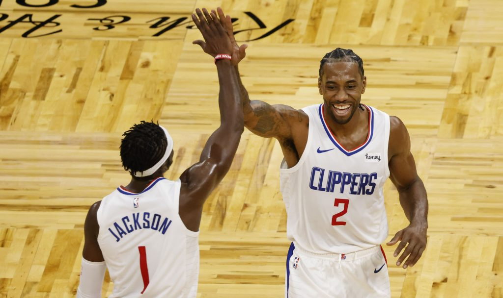 LA Clippers guard Reggie Jackson (1) and forward Kawhi Leonard (2) celebrate a basket to end the third quarter against the Orlando Magic at Amway Center.