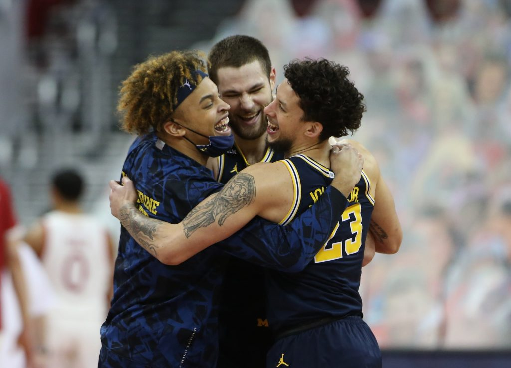 Michigan Wolverines players including Michigan Wolverines center Hunter Dickinson (center) and forward Brandon Johns Jr. (23) celebrate their win over the Wisconsin Badgers after the game at the Kohl Center