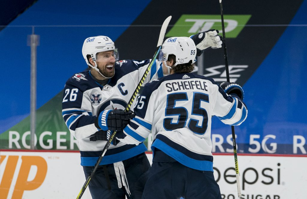 Feb 21, 2021; Vancouver, British Columbia, CAN; Winnipeg Jets forward Blake Wheeler (26) and forward Mark Scheifele (55) celebrate ScheifeleÕs goal against the Vancouver Canucks in the third period at Rogers Arena. Jets won 4-3 in Overtime.