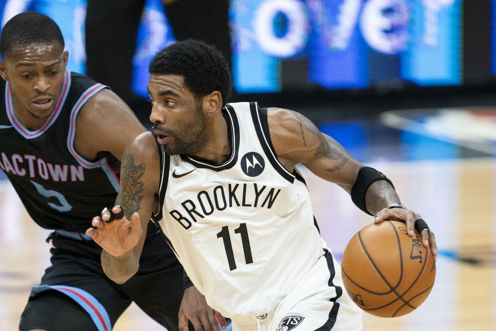 February 15, 2021; Sacramento, California, USA; Brooklyn Nets guard Kyrie Irving (11) dribbles the basketball against Sacramento Kings guard De'Aaron Fox (5) during the first quarter at Golden 1 Center