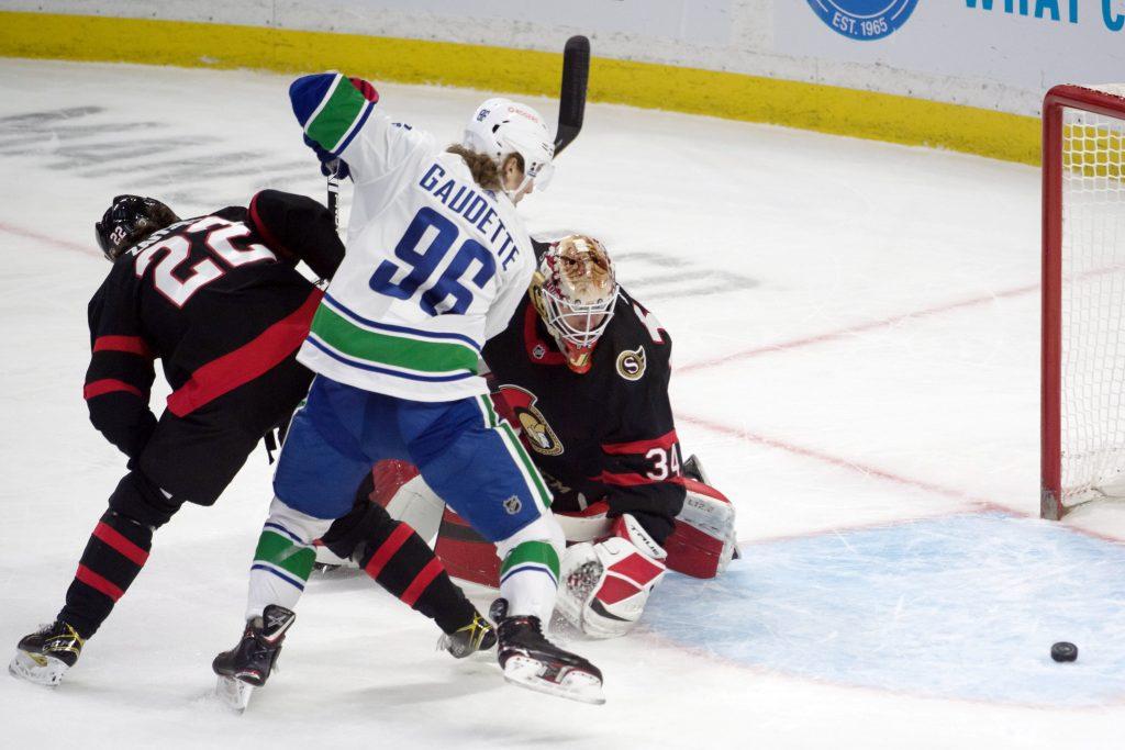 Vancouver Canucks center Adam Gaudette and Ottawa Senators goalie Joey Daccord scramble for control of the puck