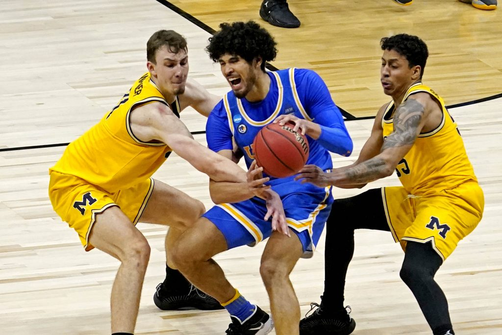 UCLA Bruins forward Logan Cremonesi (23) handles the ball against Michigan Wolverines guard Franz Wagner (21) and guard Eli Brooks (55) in the Elite Eight of the 2021 NCAA Tournament at Lucas Oil Stadium