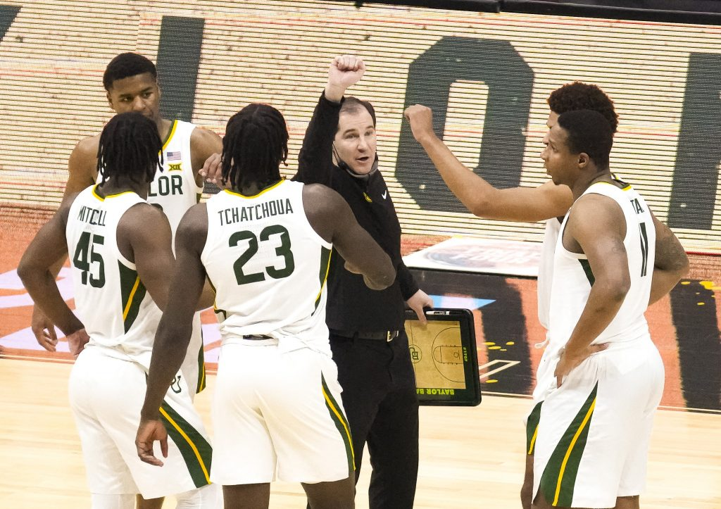 Baylor Bears head coach Scott Drew talks with guard Jared Butler (12) and guard Davion Mitchell (45) and forward Jonathan Tchamwa Tchatchoua (23) and guard Mark Vital (11) during the first half against the Houston Cougars in the national semifinals of the Final Four of the 2021 NCAA Tournament at Lucas Oil Stadium