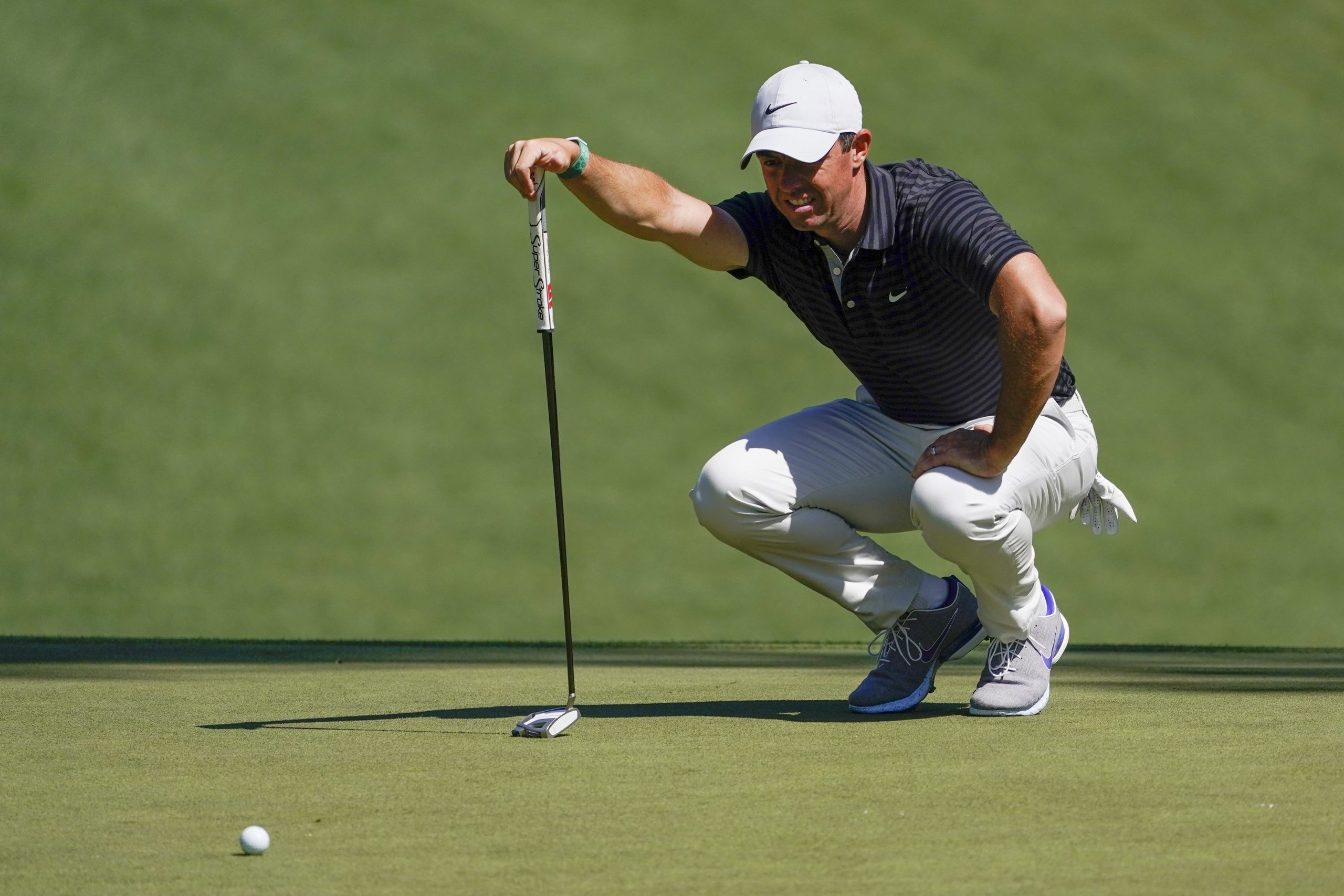 Rory McIlroy lines up a putt on the 10th green during a practice round for The Masters golf tournament at Augusta National Golf Club.