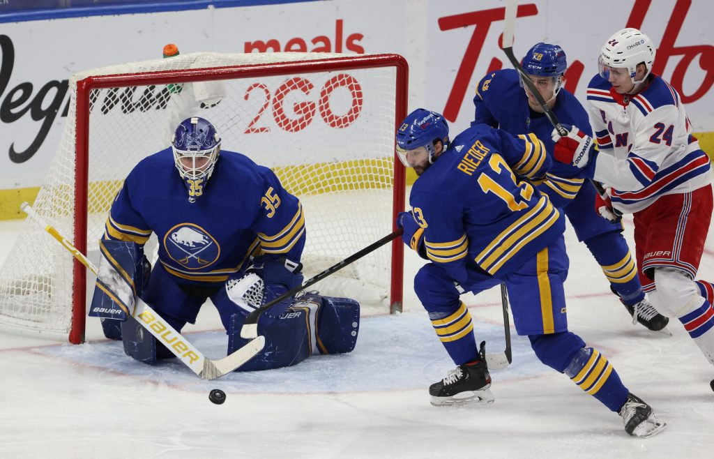 Buffalo Sabres goaltender Linus Ullmark (35) makes a save as center Tobias Rieder (13) moves to clear the puck.
