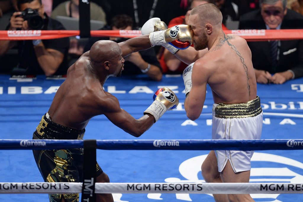 Conor McGregor (left) punches Floyd Mayweather Jr. during a boxing match at T-Mobile Arena.
