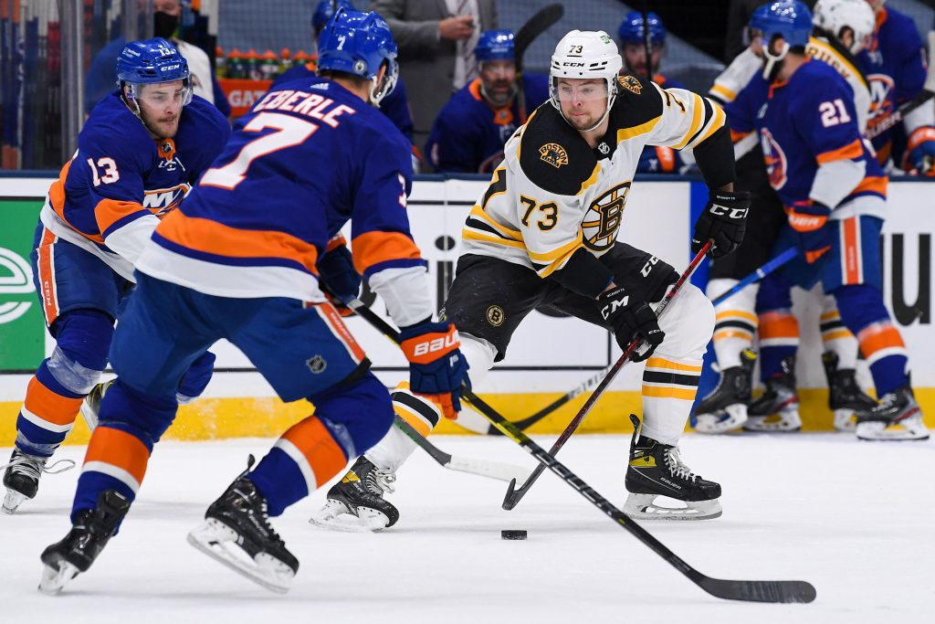 Jun 5, 2021; Uniondale, New York, USA; Boston Bruins defenseman Charlie McAvoy (73) controls the puck against New York Islanders center Mathew Barzal (13) and New York Islanders right wing Jordan Eberle (7) during the first period in game four of the second round of the 2021 Stanley Cup Playoffs at Nassau Veterans Memorial Coliseum.