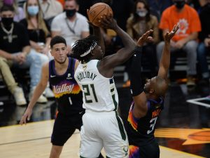 Milwaukee Bucks guard Jrue Holiday (21) shoots against Phoenix Suns guard Chris Paul (3) during the first half in game one of the 2021 NBA Finals at Phoenix Suns Arena