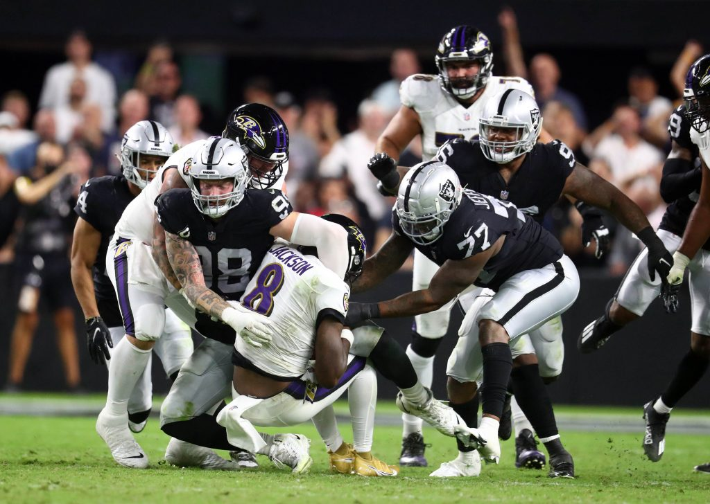 Baltimore Ravens quarterback Lamar Jackson (8) is brought down by Las Vegas Raiders defensive end Maxx Crosby (98) and defensive end Quinton Jefferson (77) during the second half at Allegiant Stadium